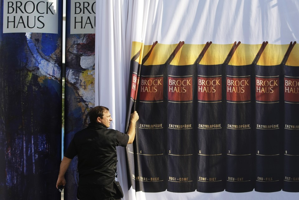 "A worker hangs up a curtain to cover an installation showing the encyclopedia of German publishing house ""Brockhaus"" designed by German actor Armin Mueller-Stahl one day ahead of the official opening of the Frankfurt book fair, October 8, 2007.  REUTERS/Kai Pfaffenbach (GERMANY) - RTR1UPH1"