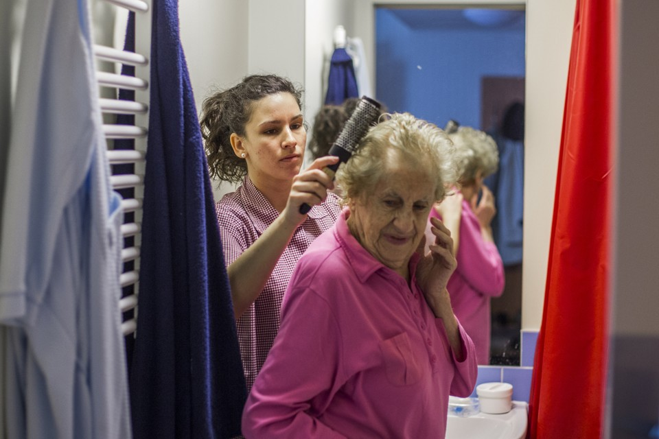 Alba Gil Quiros (L) from the Spanish island of Tenerife brushes a resident's hair at the SenVital elderly home in Kleinmachnow outside Berlin May 28, 2013. Facing an acute shortage of skilled applicants among its own workforce, German institutions in the care sector increasingly turn to southern European countries to hire trained nursing staff who are willing to work abroad despite the language barrier in order to escape unemployment at home. The SenVital home for the elderly outside Berlin has accepted five qualified nurses from Spain as their staff, providing eight months of language training and additional care schooling needed to attain the German nursing concession.  Some 100 Spaniards applied for the ten vacancies SenVital had advertised across its various houses.  REUTERS/Thomas Peter (GERMANY  - Tags: HEALTH BUSINESS EMPLOYMENT) - RTX103ZO