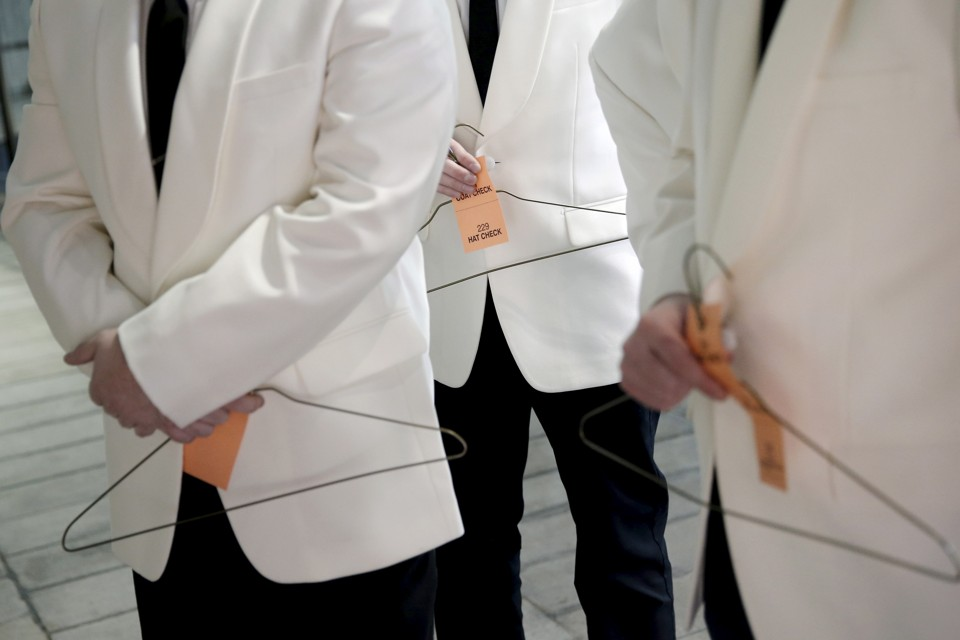 "Uniformed attendants hold coat hangers to check coats for guests arriving for the ""An Evening Honoring Valentino"" gala benefiting the Lincoln Center Corporate Fund at Alice Tully Hall at Lincoln Center in the Manhattan borough of New York City, December 7, 2015. The event honored Valentino Creative Directors Maria Grazia Chiuri and Pierpaolo Piccioli.  REUTERS/Mike Segar - RTX1XNFY"