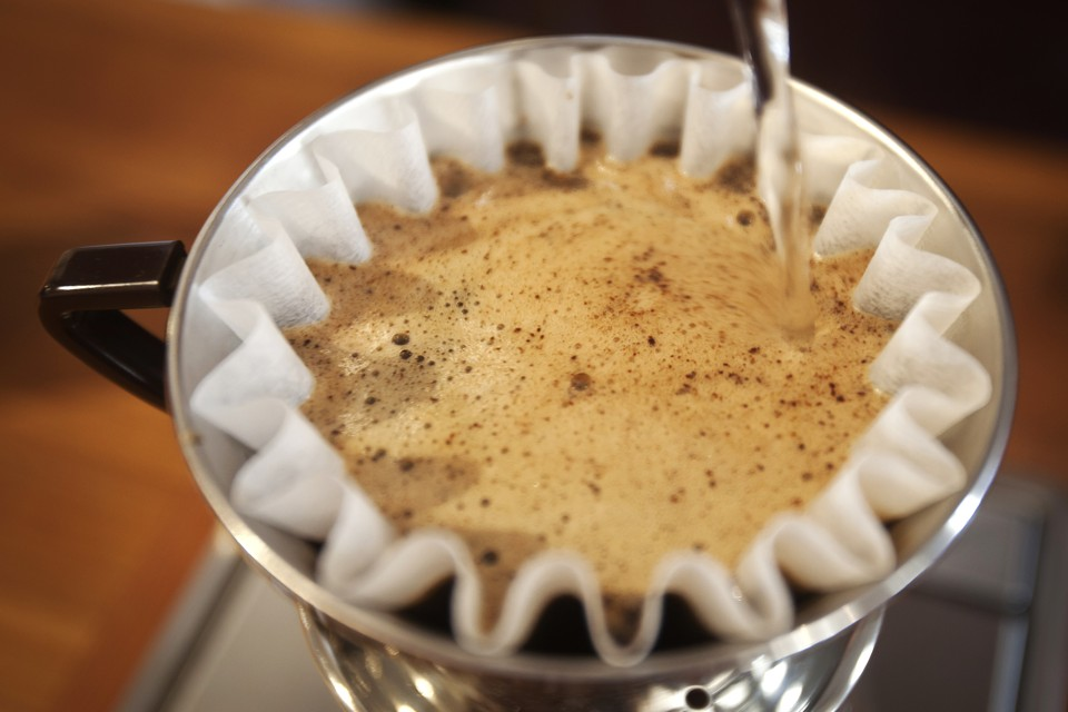 Hot water is poured onto La Bendicion coffee from Nicaragua in a coffee filter, at Irving Farm in the Manhattan borough of New York September 23, 2014. Coffee roasters are buying coffee beans in bulk from Colombia, exploiting low comparative prices and reflecting new flexibility by U.S. roasters who had become over reliant on a single country for premium arabica. To match story USA-COFFEE/ROASTERS     Picture taken September 23, 2014.   REUTERS/Carlo Allegri (UNITED STATES - Tags: SOCIETY) - RTR48KLZ