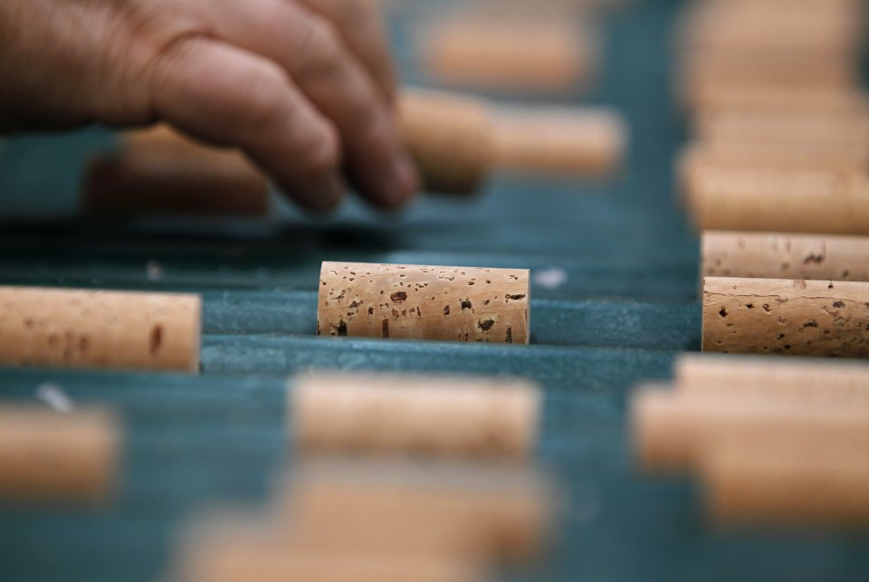 "Portugal Cork's Comeback - A worker picks a cork stopper in a quality control line at a factory in Santa Maria de Lamas, northern Portugal, July 19 2011. Women sitting next to conveyor belts of stoppers check for tiny defects such as ""split ends"" and ""worm holes"" that might let air seep into a bottle and spoil the wine. (AP Photo/Armando Franca)"