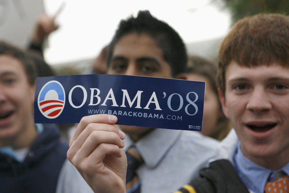 A student holds an Obama bumper sticker at the Tatnall School near Wilmington, Delaware November 4 2008. REUTERS/Tim Shaffer  (UNITED STATES)  US PRESIDENTIAL ELECTION CAMPAIGN 2008 (USA) - RTXA8I3