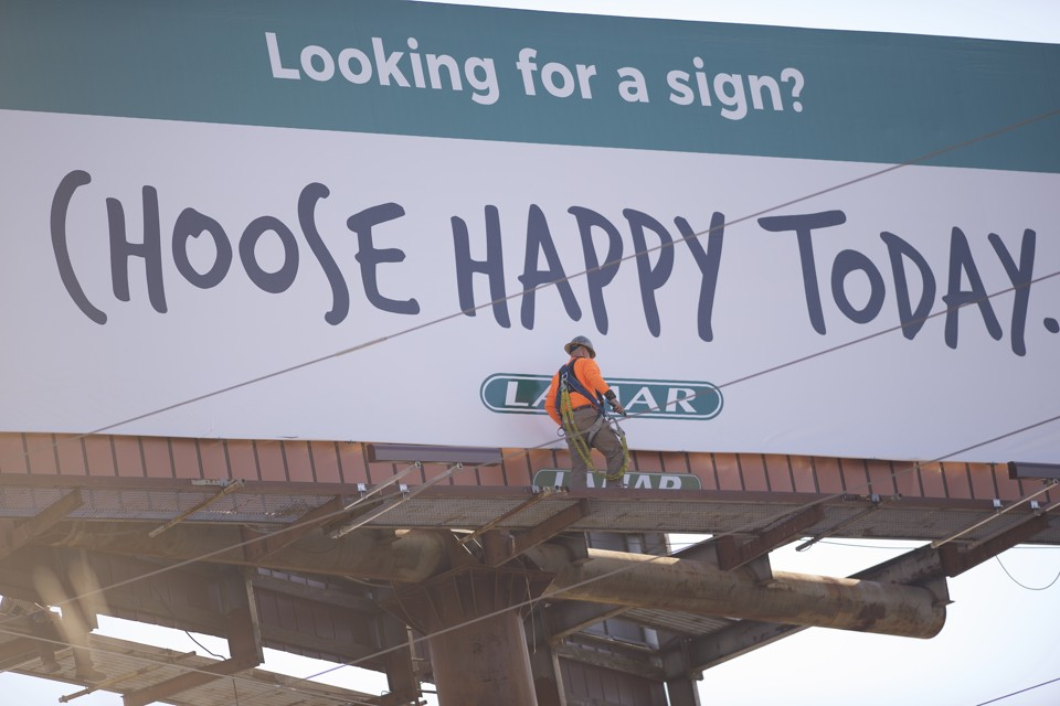 "CAYCE, SC - FEBRUARY 27:  A worker makes adjustments on a billboard stating ""Choose Happy Today,"" along Interstate 77 during the South Carolina Democratic Presidential Primary February 27, 2016 in Cayce, South Carolina.  Voters cast their ballots for the South Carolina Democratic Presidential Primary between Democratic Presidential candidates, former Secretary of State Hillary Clinton and Senator Bernie Sanders of Vermont.  (Photo by Mark Makela/Getty Images)"