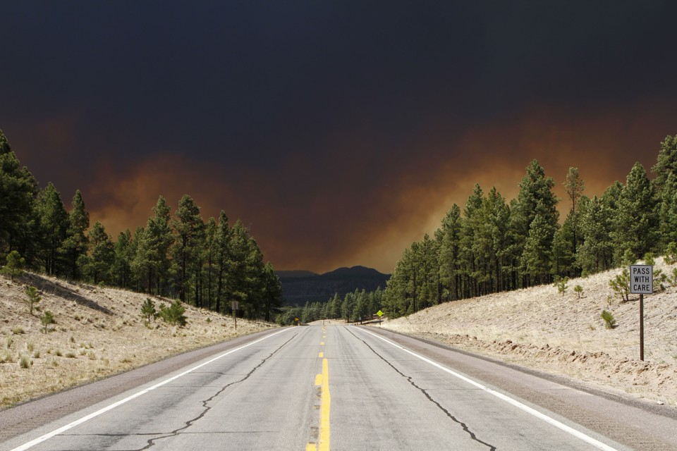 A view of the Wallow Wildfire is pictured in the distance seen along the U.S. Route 180 as smoke fills the sky in Luna, New Mexico June 6, 2011. A wildfire that has charred more than 350 square miles (906 sq km) in eastern Arizona forced the evacuation of a third town on Monday and crept near populated areas along the New Mexico border as it raged out of control for a ninth day. The so-called Wallow Fire, burning about 250 miles (400 km) northeast of Phoenix and stretching to near the Arizona-New Mexico border, ranks as the third-largest fire on record in Arizona. REUTERS/Joshua Lott (UNITED STATES - Tags: DISASTER ENVIRONMENT IMAGES OF THE DAY) - RTR2NDRO