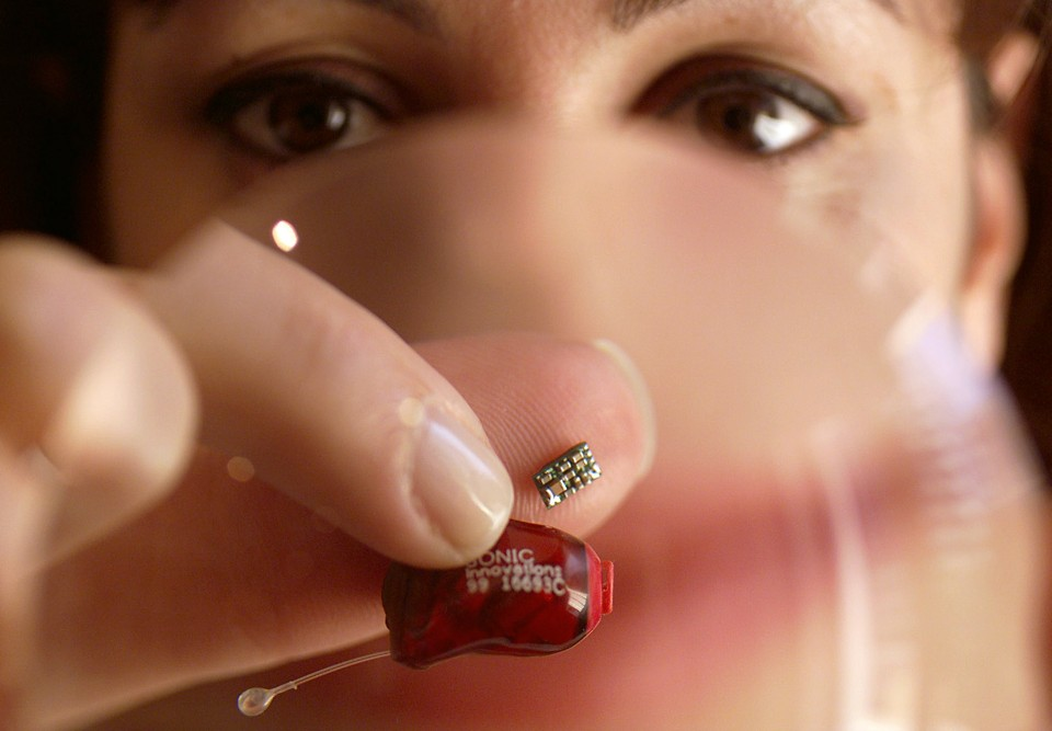 Mimi Farah holds through a magnifying glass the world's smallest microchip ever designed for a hearing aid at its launch in Sydney November 15. The chip can process sounds around 90 percent faster than traditional hearing aids and contains nine audio channels, similar to a graphic equalizer on a home stereo system, that can be individually controlled to suit the owner's personal requirements.    DG/PB/JP - RTRSDK7