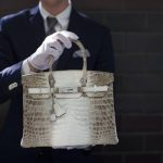 An employee holds an Hermes diamond and Himalayan Nilo Crocodile Birkin handbag at Heritage Auctions offices in Beverly Hills, California September 22, 2014. The handbag has 242 diamonds with a total of 9.84 carats.  REUTERS/Mario Anzuoni  (UNITED STATES - Tags: ENTERTAINMENT FASHION TPX IMAGES OF THE DAY) - RTR47B6T
